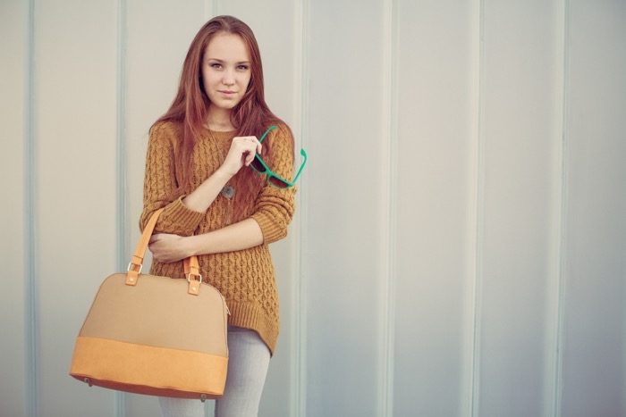Beautiful redheaded girl with fashionable big bag standing near gray wall